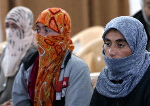 Yazidi women look on at Al-Tun Kopri health centre, located half way between the northern Iraqi city of Kirkuk and Arbil, after they were released with around 200 mostly elderly members of Iraq's Yazidi minority near Kirkuk on January 17, 2015 after being held by the Islamic State jihadist group for more than five months. Medical teams from the Kurdistan Regional Government carried out blood tests and provided emergency care to the group of Yazidis, many of whom looked sick and distraught. Yazidi officials and rights activists say thousands of members of their Kurdish-speaking community are still in captivity. AFP PHOTO / SAFIN HAMID
