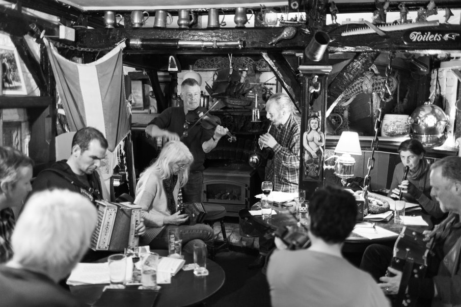 Black and white photograph by Lee J Palmer of musicians playing at the Admiral Benbow pub showing a torn Cornish flag in the background.