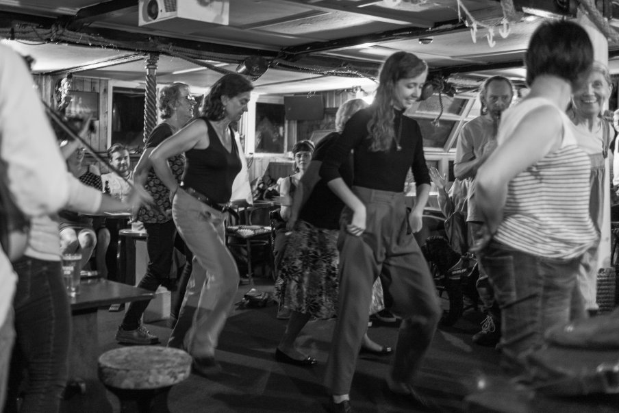Black and white photograph by Lee J Palmer of dancers dancing to musicians playing at the Admiral Benbow pub.