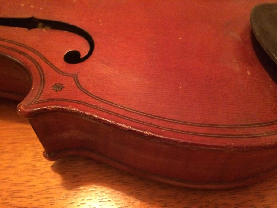 Detail of a violin showing double purfling or edge decoration and a star or flower symbol in one of the corner bouts.