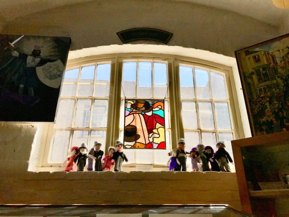 Window of museum with a stylised stained glass of dancers, colourful, and knitted dancing figures on window sill.