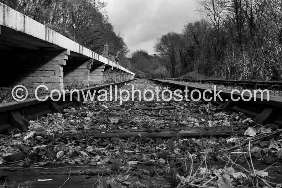 Low level view of railway line with the sleepers and rails stretching off into the distance. Platform sits high in this black and white image
