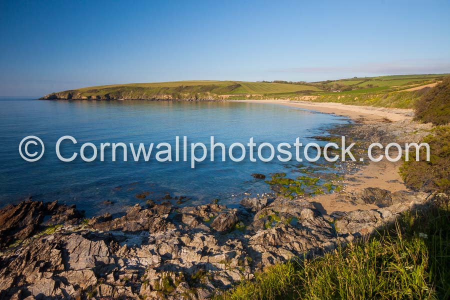 Towan Beach In Early Morning Sunshine With Foreground Rocks