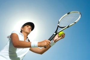 Woman holding a tennis racquet ready for a serve with the sun behind her