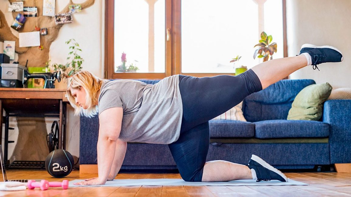 Woman doing strength training exercises on the floor of her living room