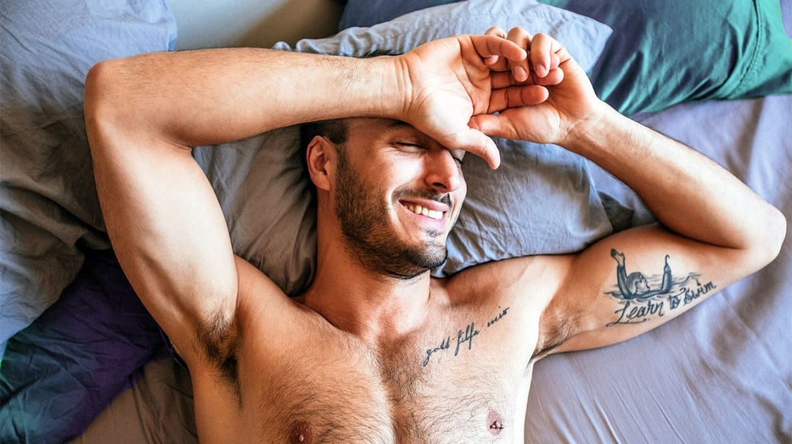cropped, chest up view of a person laying shirtless in bed, arms above their head and hands resting on their forehead