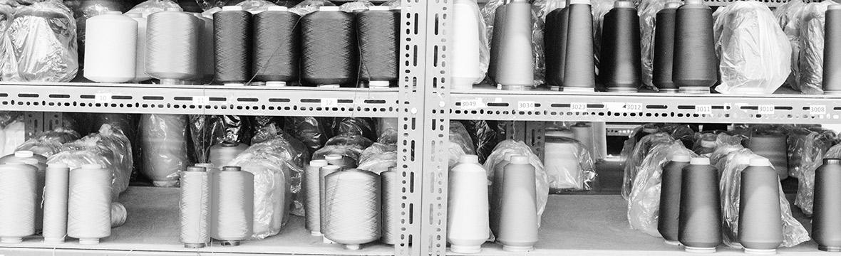 Regal mit großen Fadenspulen zur Produktion von Strümpfen