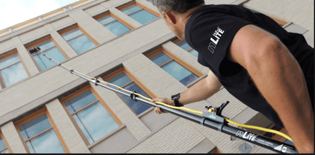 Commercial Window Cleaning Equipment Reaching High Building Window in Grand Rapids
