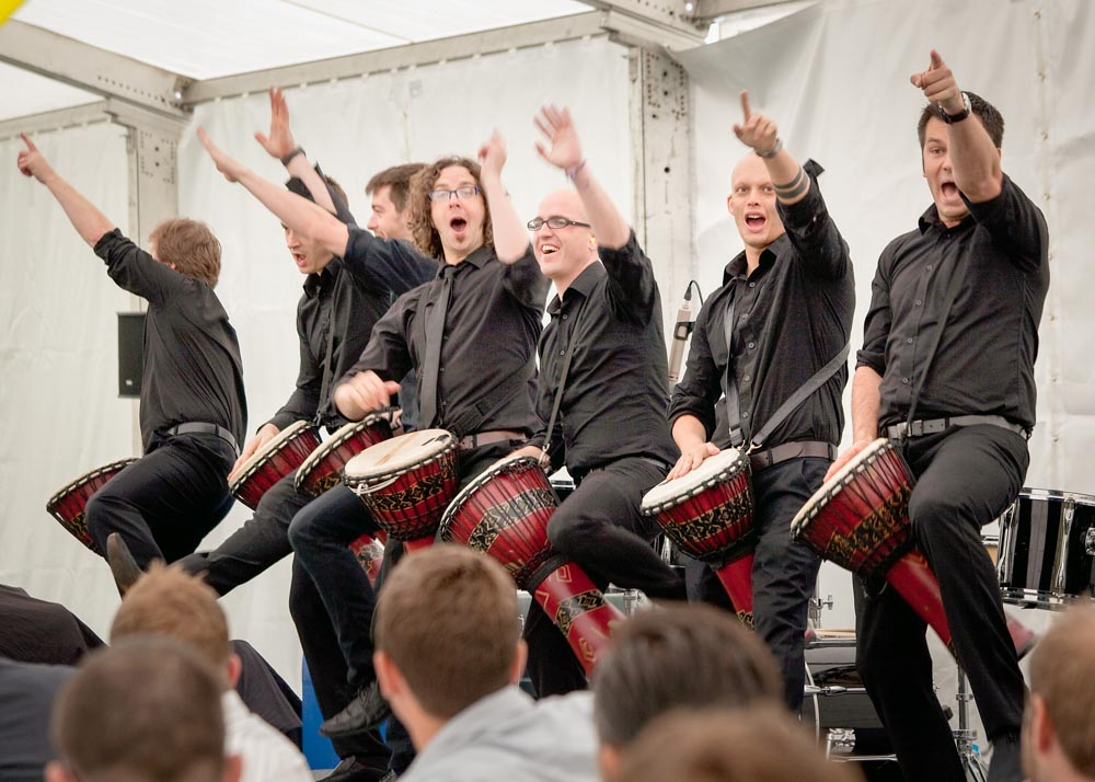 Seven drummers in black onstage at a corporate hospitality event