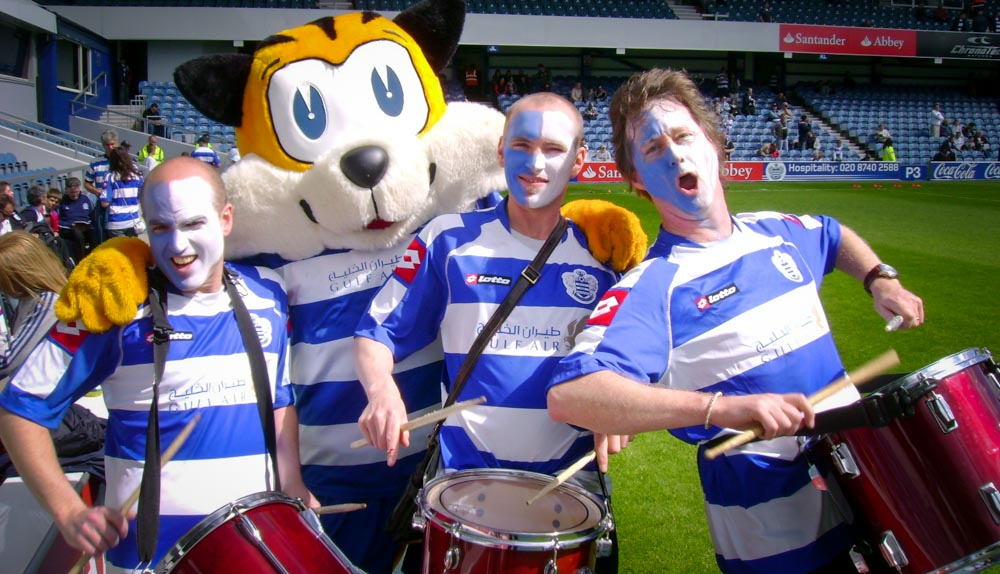 Facepainted drummers on a sports pitch with a mascot - family fun days