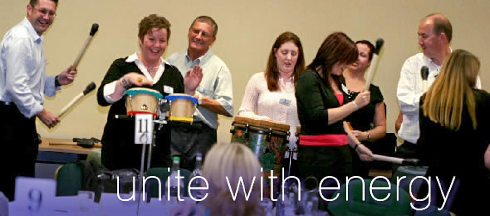Happy people playing a variety of instruments in a percussion workshop team building activity