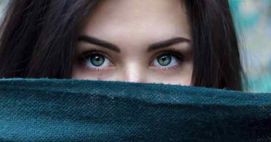 stock photo of a woman's eyes with her face covered by a scarf.