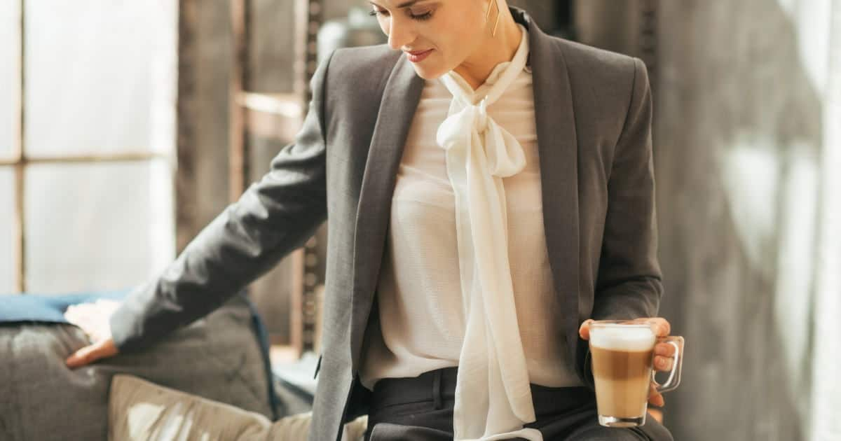 stylish tops for under women's suits - stock photo of a young woman wearing a bow blouse under a suit