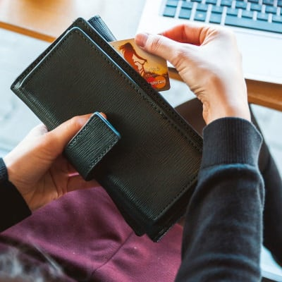 stock photo of woman pulling credit card out of wallet
