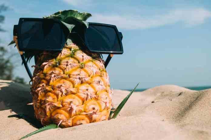 Un ananas avec des lunettes de soleil sur le sable