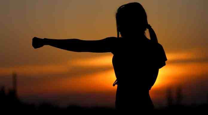 Femme faisant du karate dans un couche de soleil