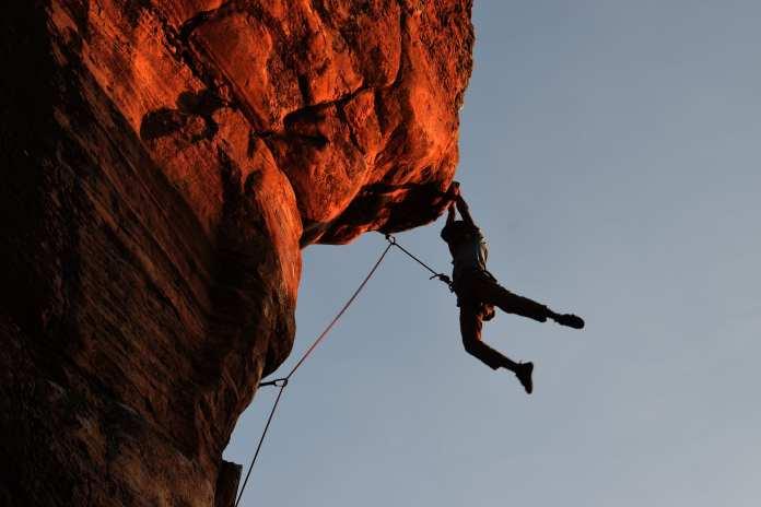 Homme suspendu à un rocher