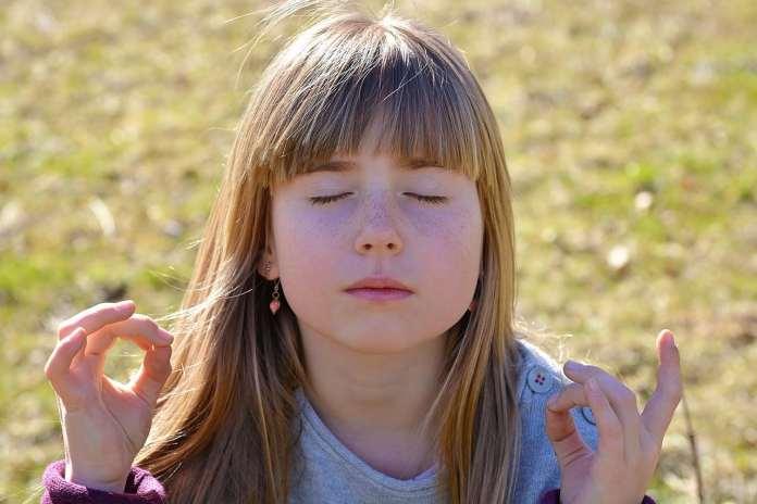 Enfant méditant dans l'herbe