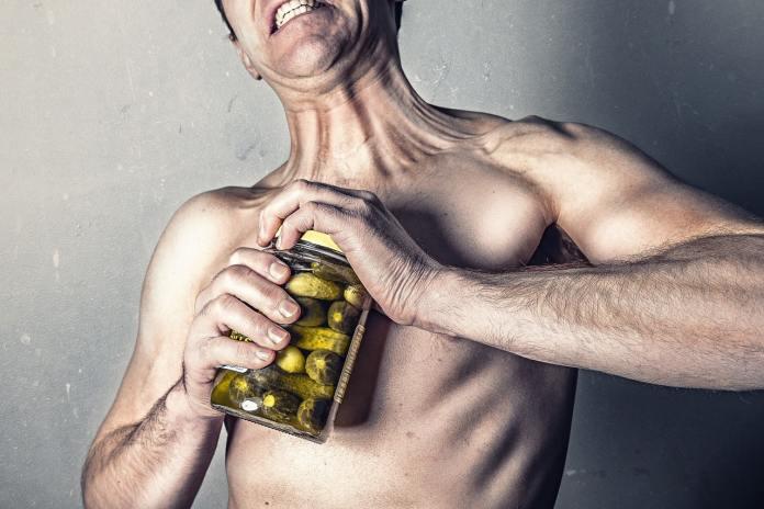 Homme ouvrant un pot de cornichons