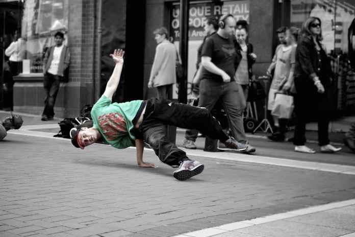 Homme faisant une figure de street workout / break dance dans la rue