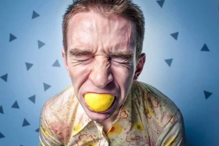 Homme qui mord dans un citron