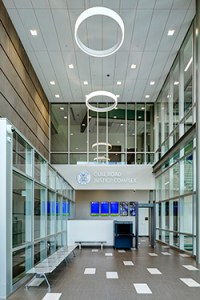 A two-story glass curtain wall stretches the length of the public corridors, creating an abundance of natural light.