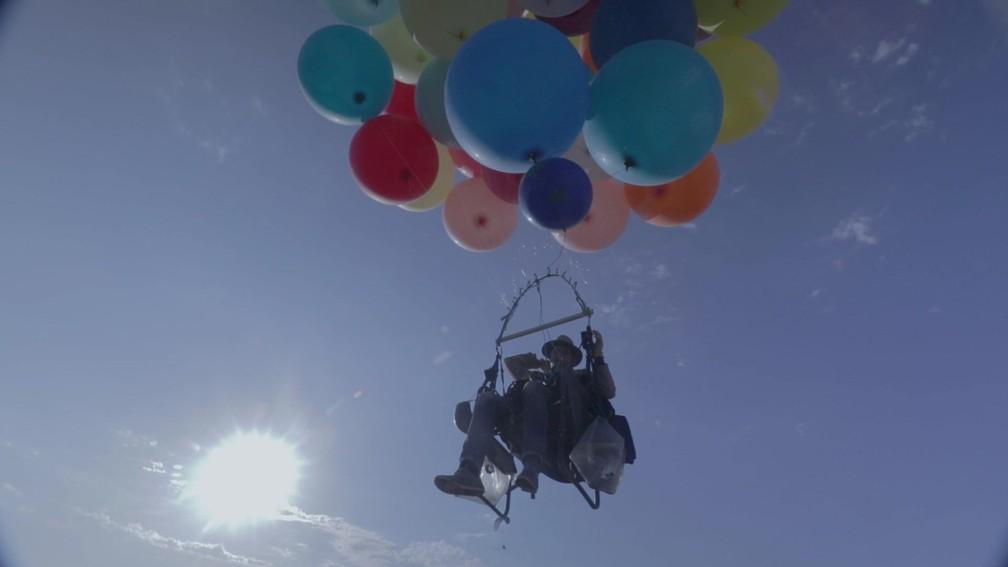 Aventureiro cruza céu da África do Sul em cadeira presa a 100 balões