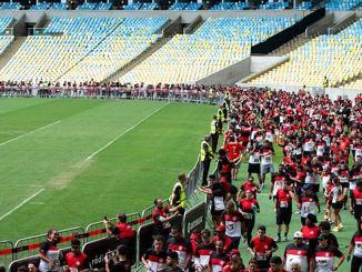 Participantes da corrida do Flamengo, a Nação Rubro-Negra em Movimento, no gramado do Maracanã