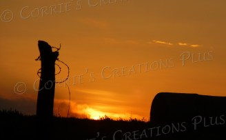 A hay bale and fencepost accentuate this sunset in southeastern Nebraska.