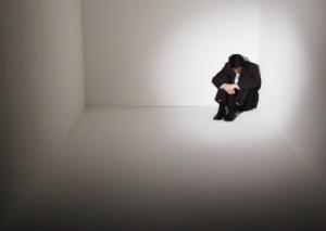 Homem sentado no canto de um quarto