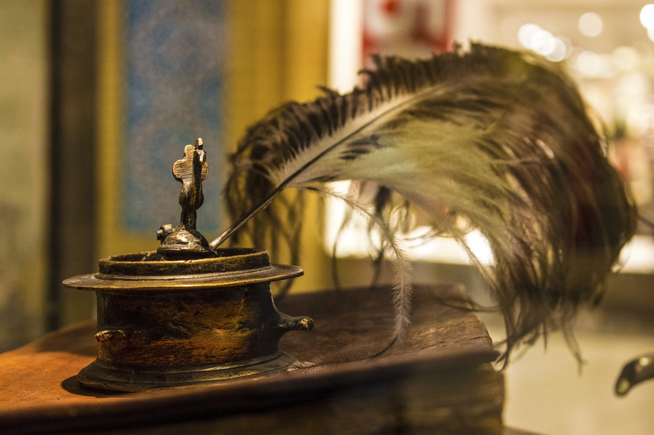 A feather pen sitting in an inkwell on a beautifully polished desk