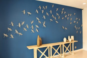 """Xavier Cortada, """"Dragonflies on Blue,"""" brushed aluminum cut-outs, 2014."""