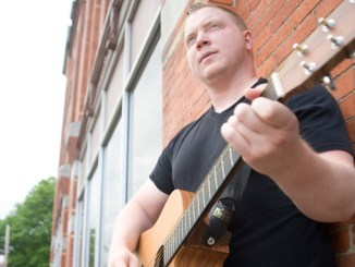 """Dana Twigg stands with his acoustic guitar Tuesday outside the Cortland Standard building in Cortland. The local musician has released his third album. """"Better View,"""" seen below. On the cover is his grandfather."""