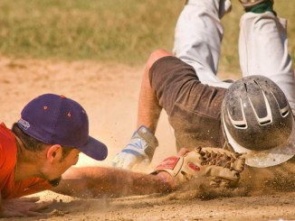 Crush third baseman Paul Ludden makes a diving tag on Sherrill baserunner Dylan Pounds who was attempting to stretch a double into a triple during the first game of Thursday's double-header on Greg's Field.