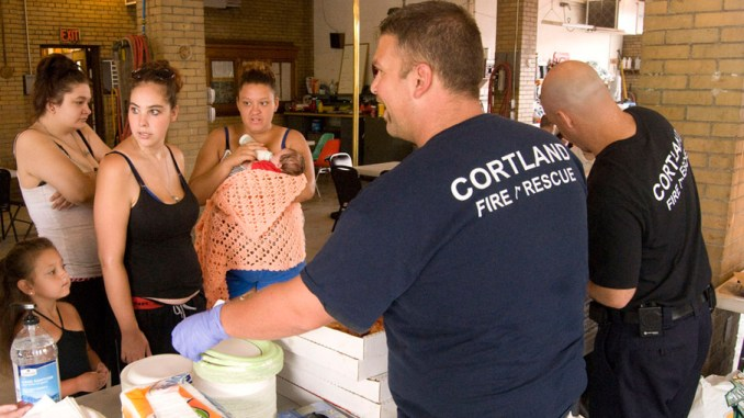 Cortland Fire Department members Dustin Contri and Jim Zelsnack hand out free pizza Monday at their main station on Court Street to help out the Loaves and Fishes organization, which couldn't serve its daily lunch program because of Friday's fire at the Grace and Holy Spirit Church, located next to the fire station. Waiting for their lunch are, left to right, 4-year-old Heaven Henry, Lisa Walker, Pam Weeks and Tiana Fink with baby Ariel Weeks.