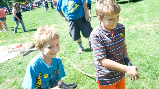 Eight-year-old Nathan Cotton, left, and his brother Aubrey Bell, 10, right, of Cortland, work together to put out a fire started by Cortland Fire Captain Dave Jensen, center, Saturday at the Cortland Comeback event at Courthouse Park in Cortland.