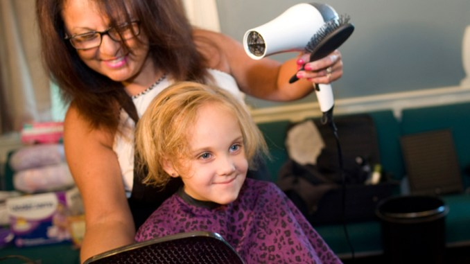 Owner of Vickie's Hair Fashion, Victoria Riccardi, of Cortland, styles seven-year-old Breanna Wing's hair Saturday during a back to school event at Believers' Chapel in Cortland.