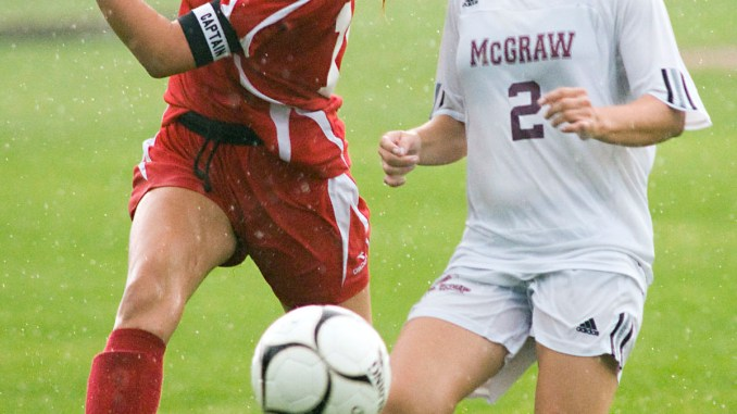 Despite a heavy rainfall, Ciara Zeeuw, of Cincinnatus, left, boots the ball upfield as Marissa Jenney, of McGraw, closes in Thursday.
