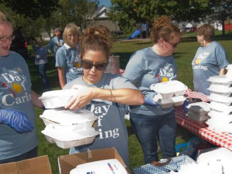 Courtney Peters, Jennifer Geibel and Jenny Robinson box up barbecue chicken dinners during a Day of Caring event at Beaudry Park Wednesday.