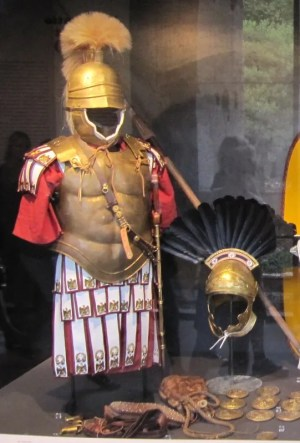 Equipment of a Republican military tribune. On the right is the helmet of a centurion. Note the transverse crest.