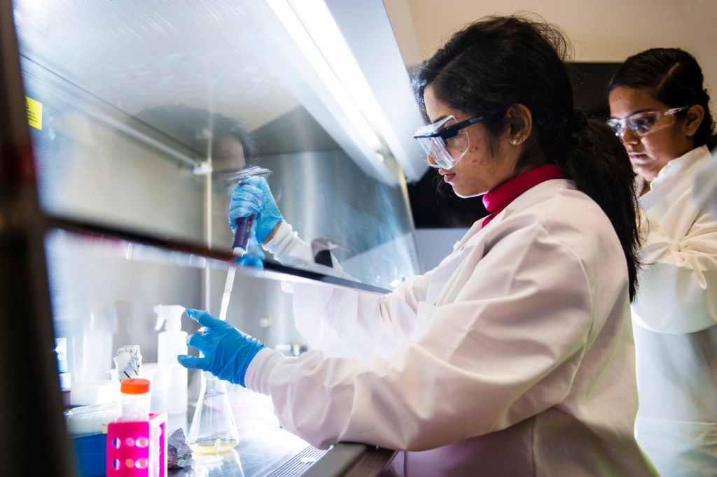 A female scientist works at a hood.
