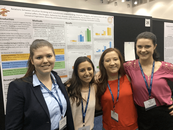 Four scientists stand in front of their research poster at the conference