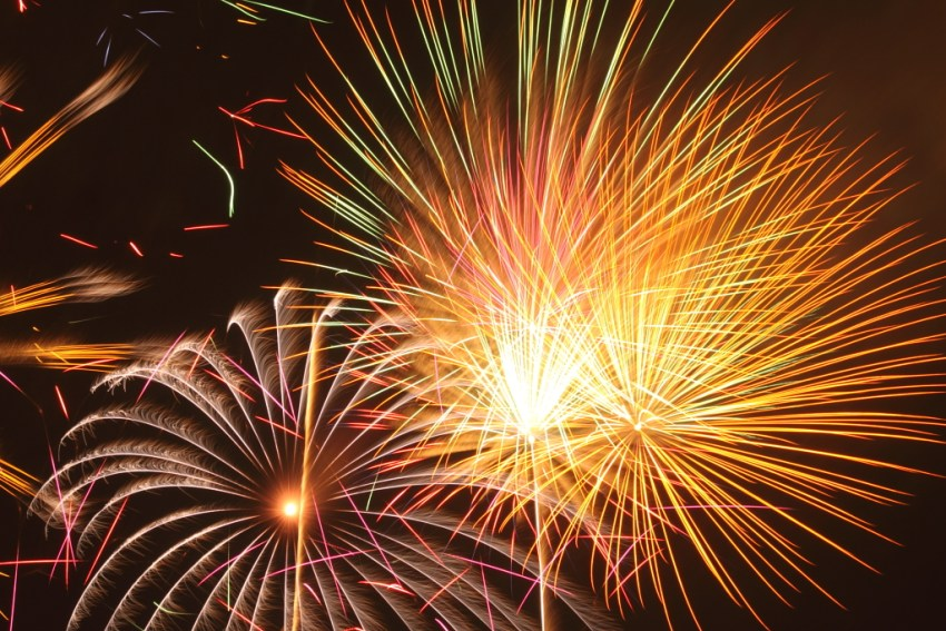 Yellow and red fireworks exploding in a dark sky