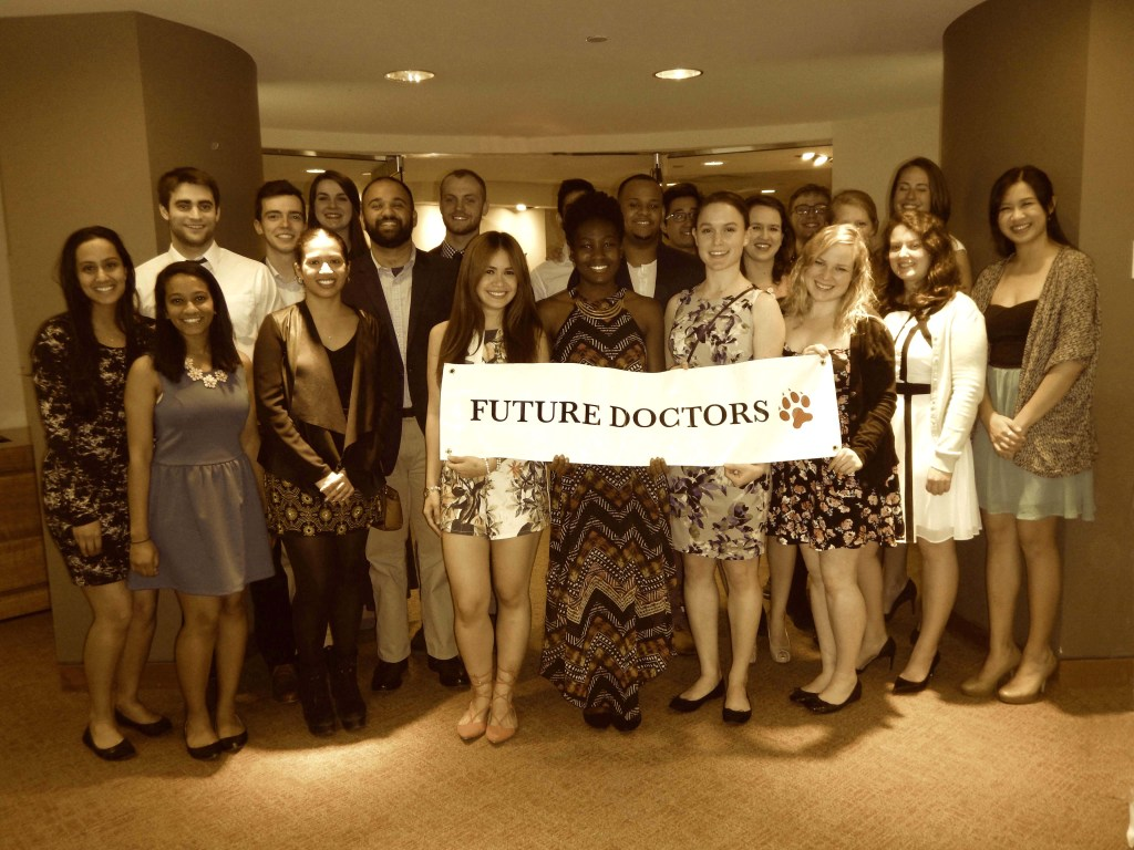 "Group of students standing together with a sign that reads ""Future Doctors."""