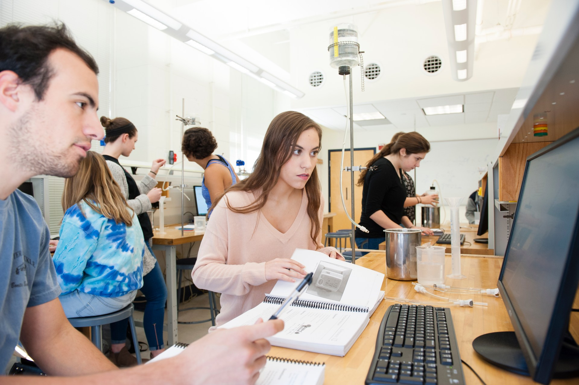 A male and female student look at their computer screen while conducting a physics experiment in lab. Other students are in the background conducting the same experiment.