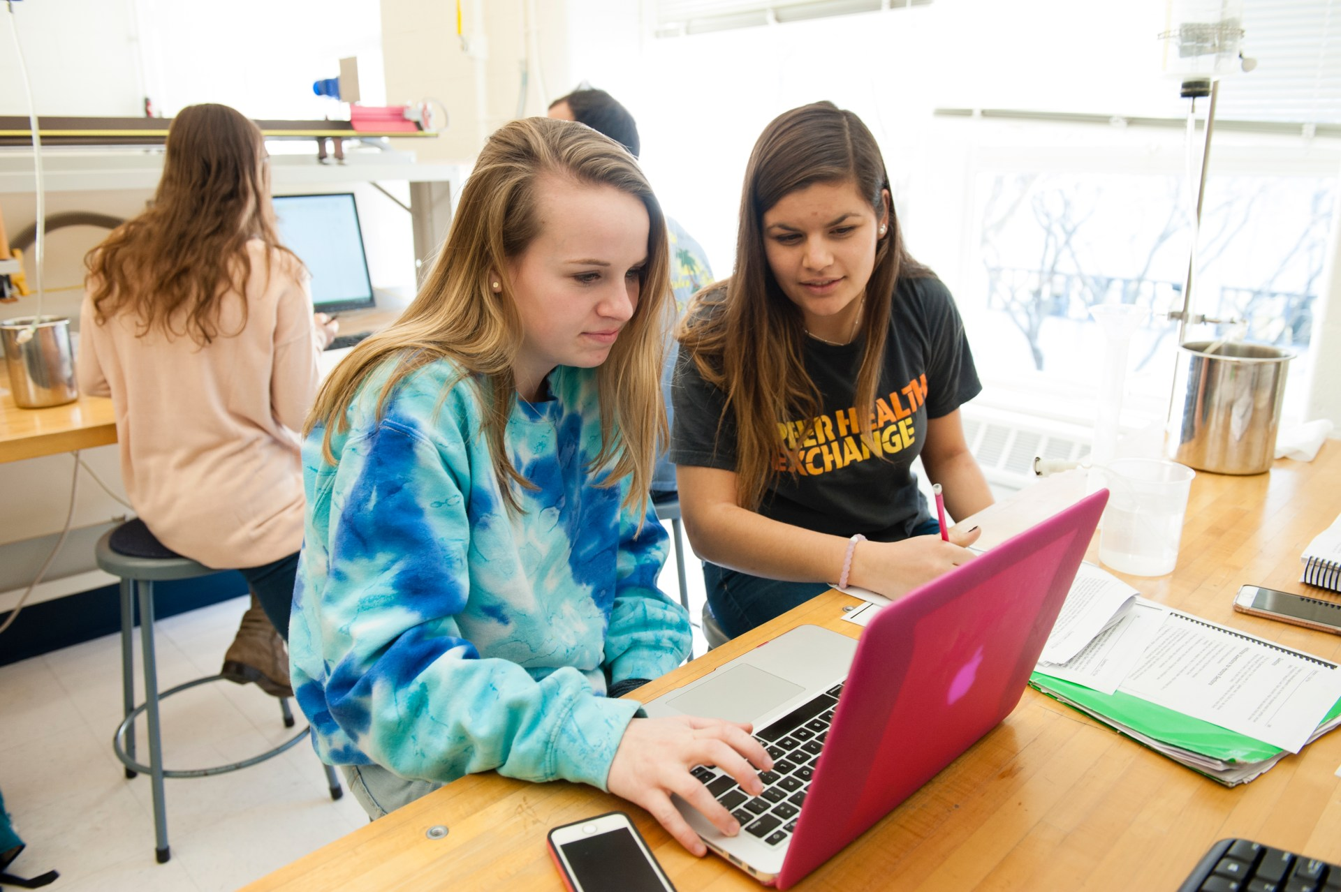 Two female students work on a physics lab. They are both looking at the screen of a laptop. Another group of students can be seen in the background working on the physics lab.