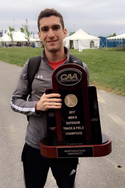 Daniel Bassous holding a track and field trophy
