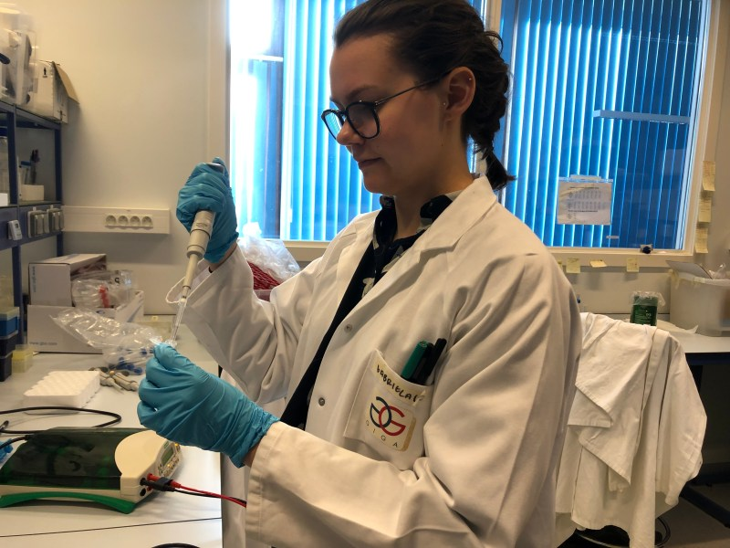 Photo of Ella Bursting using a micropipette in a lab setting.
