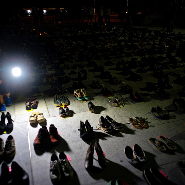 A child illuminates hundreds of shoes at a memorial for those killed by Hurricane Maria, in front of the Puerto Rico Capitol, in San Juan, Friday, June 1, 2018. Puerto Rico's Institute of Statistics announced that it has sued the U.S. territory's health department and demographic registry seeking to obtain data on the number of deaths following Hurricane Maria as a growing number of critics accuse the government of lacking transparency. (AP Photo/Ramon Espinosa)