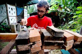 Jake Castellano, 20, of environmental studies, cleans hearth bricks in preparation for the building phase of the earth oven. His personal project at VerdEnergia is to create an oven out of sand and mud to be used by the farm and its residents.